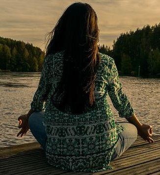 Woman Meditating at a Lake