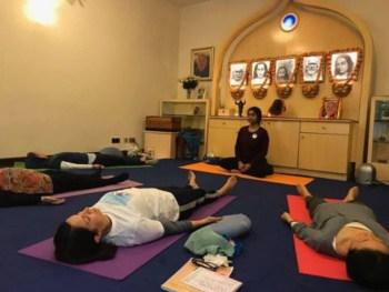 Yoga Teacher Guiding Students in Savasana